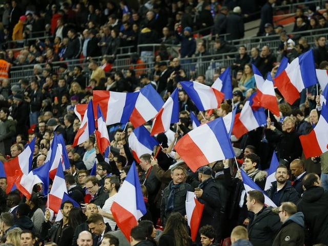 Das Publikum streckt blau/weiss/rote Fahnen in die Höhe.