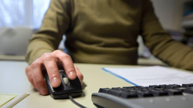 Ein Mann sitzt am Comuter, man sieht seine Hand an der Computer-Maus.