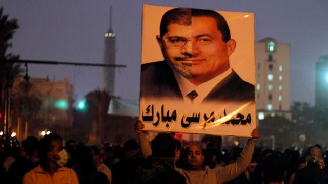 Ein Mann hält ein Plakat, auf dem je eine Gesichtshälfte von Mursi und von Mubarak zu sehen ist