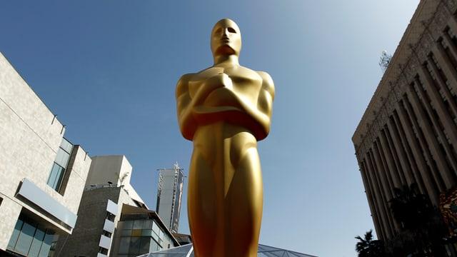 Eine riesige Oscar-Statue im Freien, Häuser im Hintergrund.