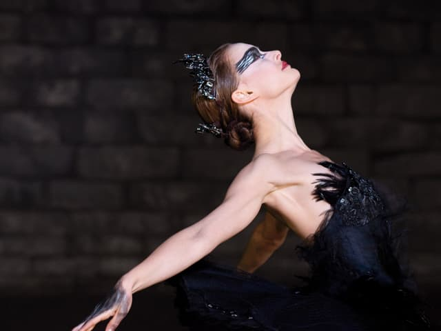 Tänzerin in schwarzem Schwan-Kostüm