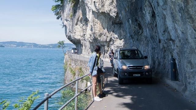 Ein Auto fährt auf einer schmalen Strasse entlang eines Felsens; Fussgänger weichen aus.