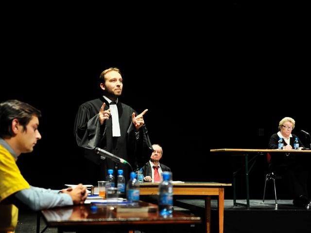 Ein Anwalt in einer schwarzen Robe gestikuliert.