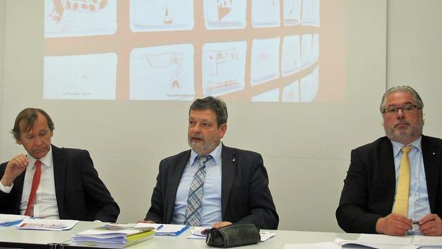 Drei Männer sitzen an einem Tisch und sprechen zum Publikum