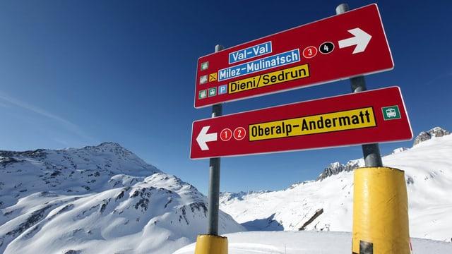 Schilder auf der Skipiste, die nach Andermatt und Sedrun weisen.