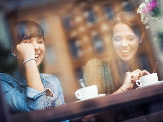 Zwei junge Frauen trinken Kaffee und lachen.