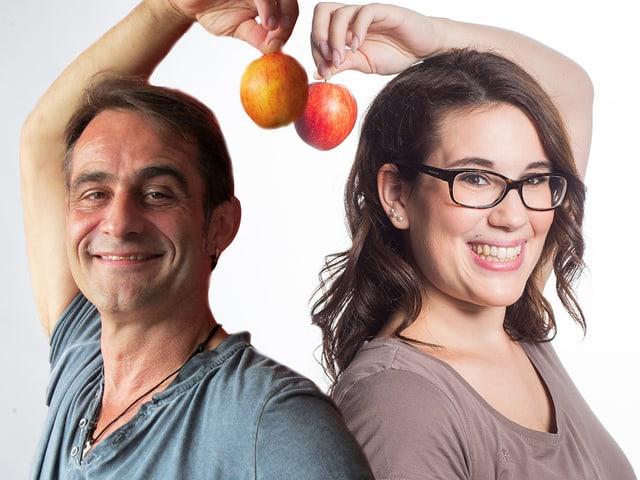 Stefanie König und Thomy Scherrer stehen Rücken an Rücken, beide halten einen Apfel in der Hand, die sie über den Kopf halten.