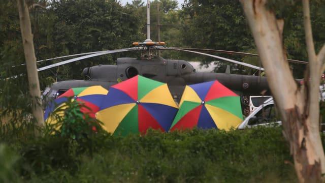 Regenschirme schirmen die letzten Buben ab, die gerettet sind und nun ins Spital geflogen werden.