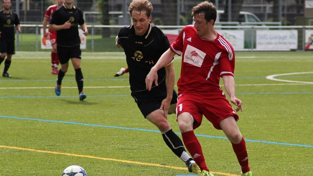 Zwei Fussballspieler kämpfen um den Ball.