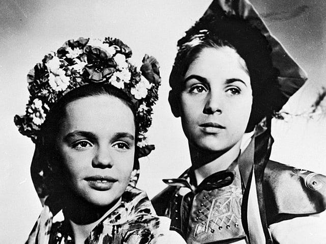 Ein Mädchen mit Blumenschmuck auf dem Kopf und ein Junge mit Kopfbedeckung.