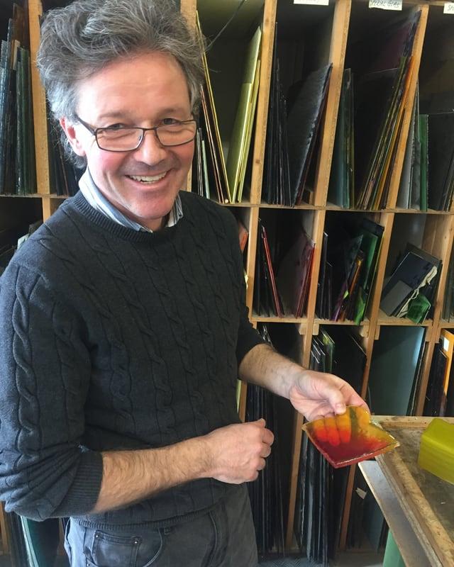 Ein Mann mit Brille hält eine kleine orange-gelbe Glasplatte in der Hand.