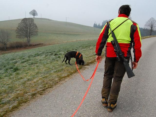 Wildhüter folgt seinem Hund an der langen Leine.