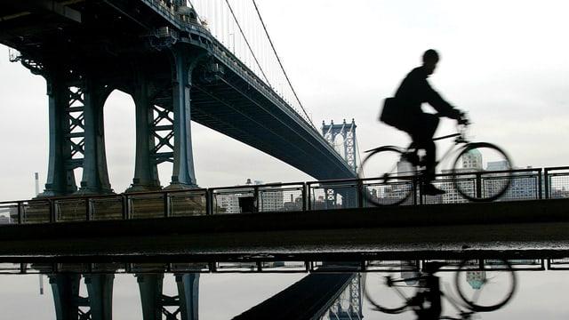 Ein Mann fährt auf dem Rad an der Brooklyn Bridge vorbei.