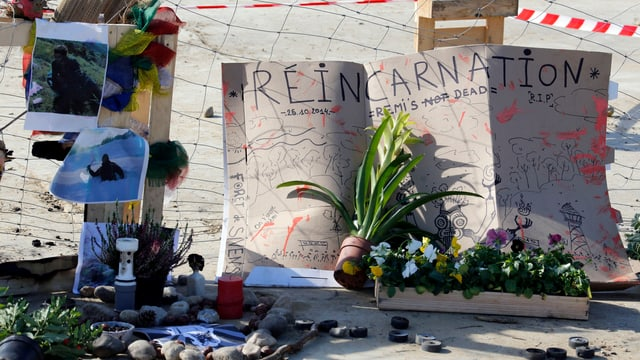 Eine Gedenkstätte für den getöteten Demonstranten mit Bildern und Blumen.
