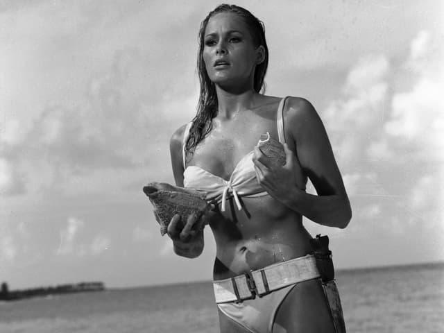 Eine blonde Frau im Bikini hält eine Muschel in der Hand und steht knöcheltief im Meer.