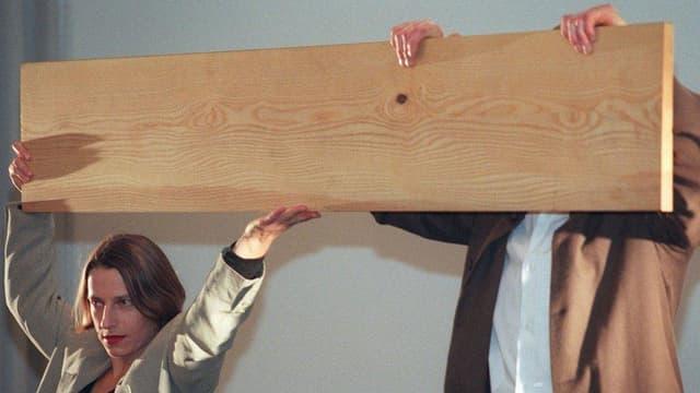 Eine Frau und ein Mann mit einem Brett vor dem Kopf.