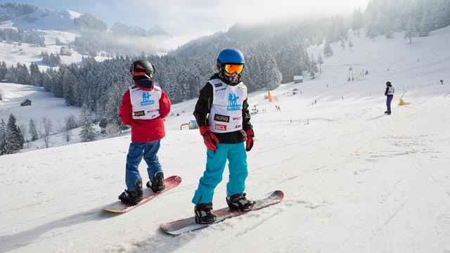Zwei Snowboarder auf verschneiten Pisten im Skigebiet Sattel-Hochstuckli.