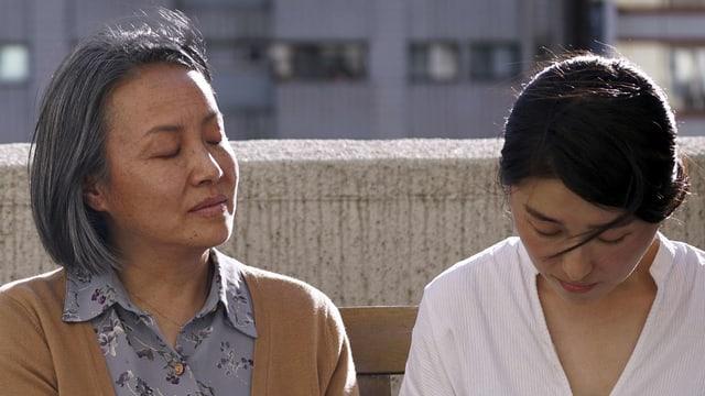 Eine ältere und eine jüngere Frau sitzen mit geschlossenen Augen nebeneinander