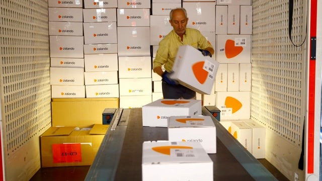 Ein Mitarbeiter von Zalando platziert zig weiss-orange Zalando-Pakete auf einem Förderband.