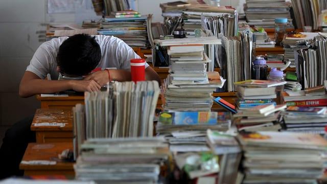 Auf Holztischen in einem Klassenraum liegen überall gestapelter Bücher, Hefte und Zettel, hinten links schläft ein Junge mit dem Kopf auf dem Tisch