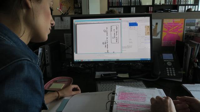 Eine Frau links im Bild schaut auf einen Ordner, der auf einem Pult liegt. Hinter dem Ordner steht ein Computerbildschirm.