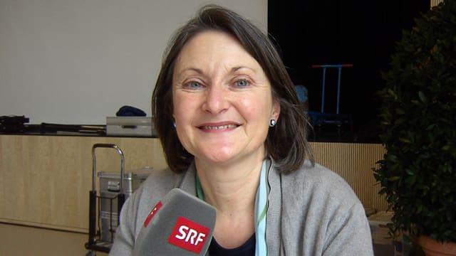 Schäfer hält ein SRF-Mikrofon in der Hand und lächelt freundlich in die Kamera. Sie hat halblange dunkle Haare.
