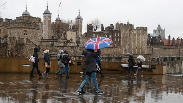 Symbolbild: Menschen vor dem London Tower, einer hat einen Regenschirm aufgespannt, der die britische Flagge zeigt.