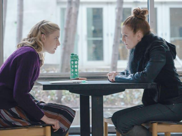 Zwei Frau sitzen sich an einem Tisch gegenüber und beugen sich vor.