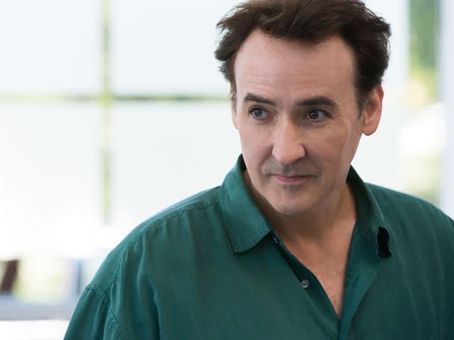 John Cusack in einem grünen Hemd.