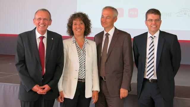 Vier Mitglieder der Regierung posieren für ein Foto.