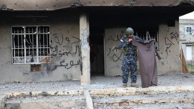Ein kurdischer Kämpfer mit dem Kleidungsstück eines IS-Kämpfers.