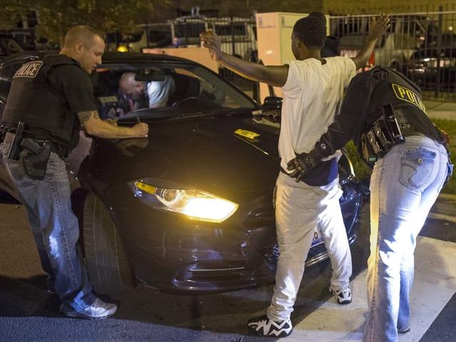 Weisse Polizisten überprüfen einen jugendlichen Afroamerikaner: Der eine Beamte tastet ihn ab, der andere schreibt auf der Kühlerhaube des Polizeiautos ein Protokoll.