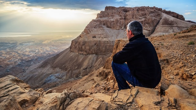 Mann sitzt auf Fels und überblickt Landschaft