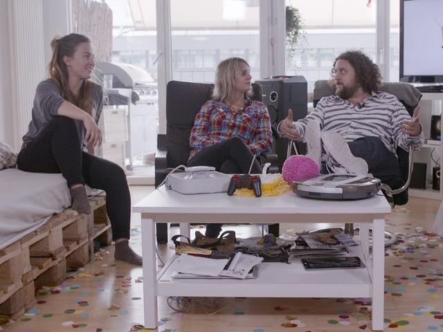 Moderator Daniel Bachmann und drei WG-Bewohner sitzen im Wohnzimmer und sprechen über die getesteten Gadgets.