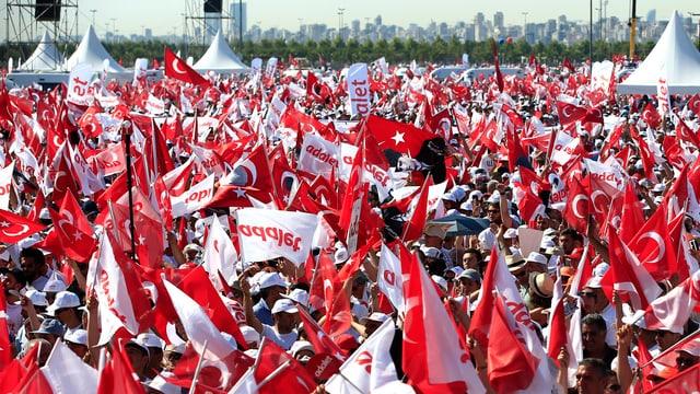 Persunas cun bandieras che sustegnan il manader da l'oposiziun tirca.