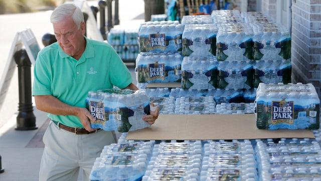 Älterer Mann nimmt 24-er Packung Halbliter-Wasserflaschen vom Stapel.