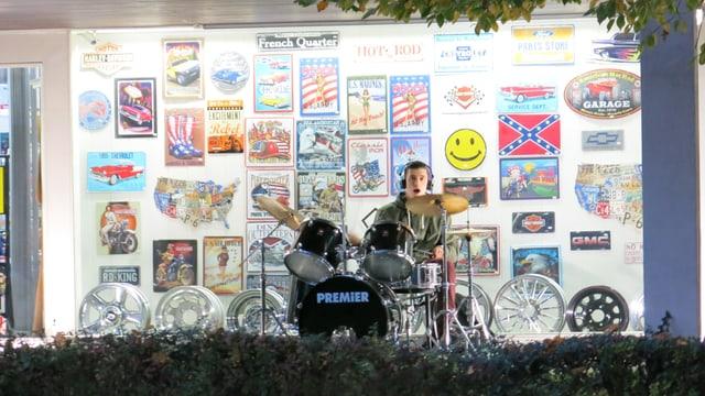 Ein junger Mann spielt Schlagzeug, vor einem Schaufenster.