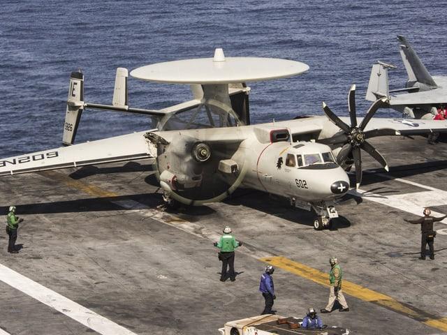 An Bord der Carl Vinson bereiten Matrosen einen E-2C Hawkeye auf den Start vor.