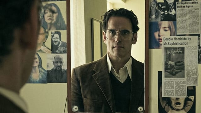 Ein Mann mit Brille betrachtet sich im Spiegel.