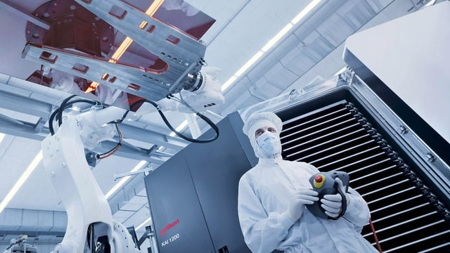 Mann bedient Maschine in der Solarproduktion