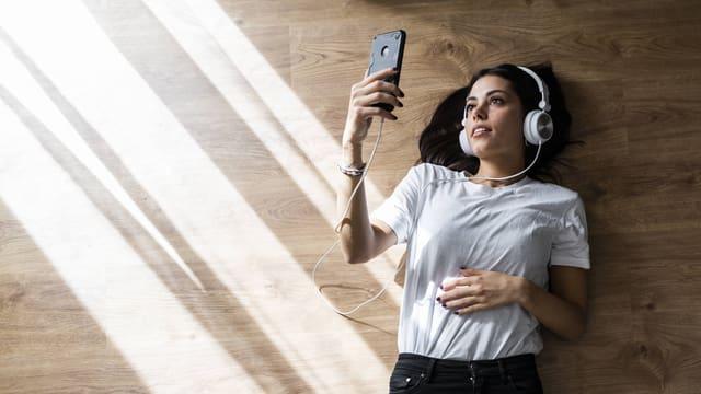 Junge Frau mit Kopfhörern blickt auf ihr Smartphone