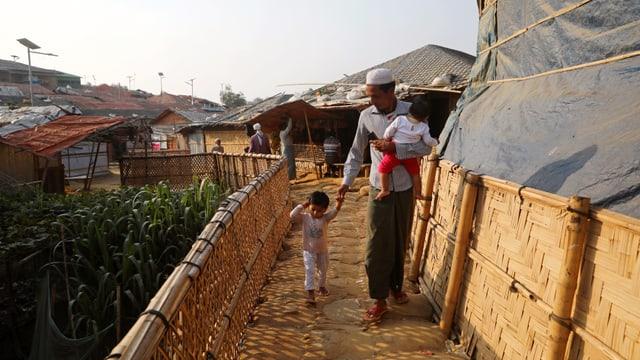 Mann mit Kind in der Hüttensiedlung.