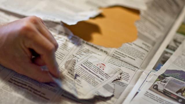 Eine Hand reisst ein Jobinserat aus der Zeitung