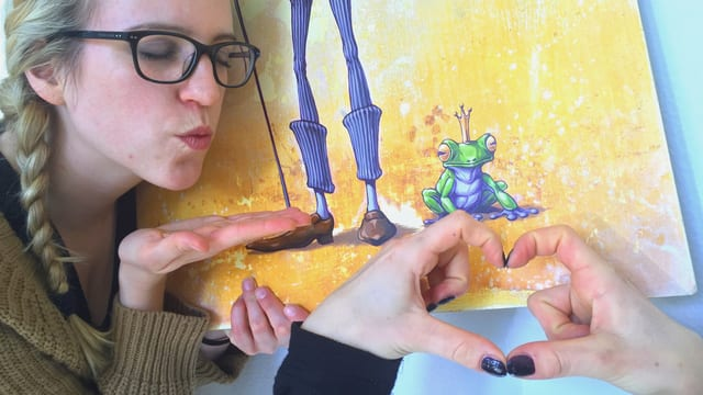 Frau mit Kussmund hält Bild eines Froschkönigs