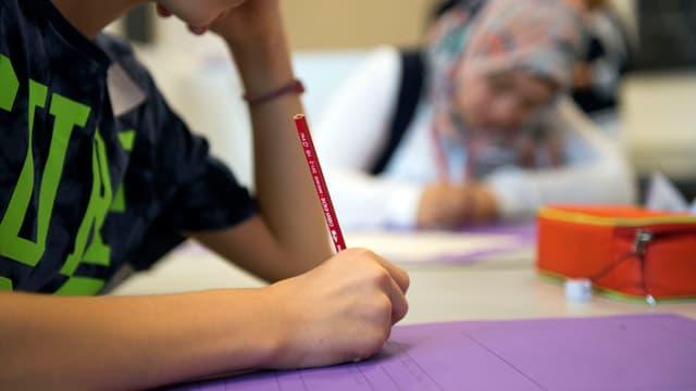 Schüler hält einen Bleistift in der Hand und schreibt.