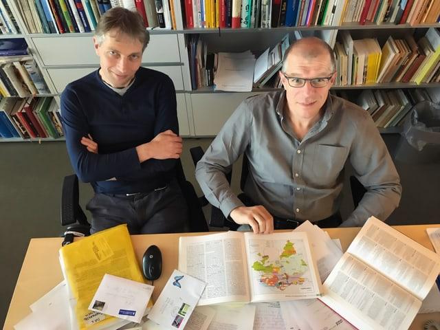 Zwei Herren sitzen vor einer Bücherwand, davor viele Briefe von Hörerinnen und Hörern.