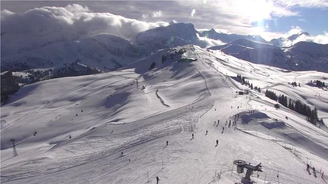 Skigebiet, dahinter die Berner Alpen, über denen die typische Wolkenmauer bei Föhn erkennbar ist.  Im Skigebiet dagegen scheint die Sonne.