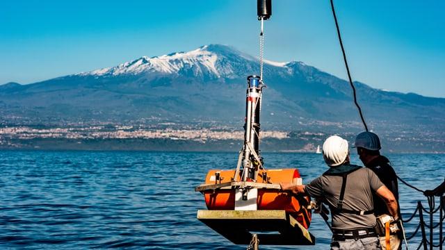 Zwei Männer auf einem Schiff, bringen ein Gerät ins Wasser