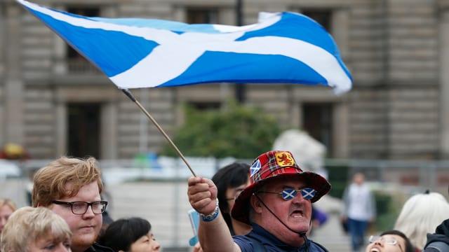 Ein Schotte mit Hut und Brille schwingt eine Schottland-Flagge