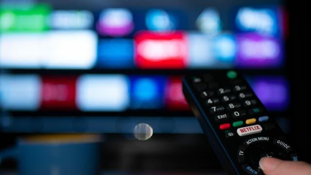 Eine Hand hält eine TV-Fernbedienung, im Hintergrund sind verschwommen bunte Apps auf einem TV-Bildschirm.